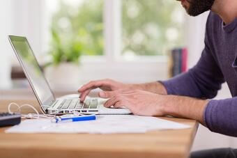 Close up low angle view of a man working from home on a laptop computer sitting at a desk surfing the internet.jpeg